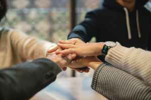 shallow focus photography of five people holding each other hands